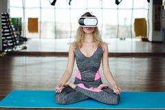Frau in der Yogaklasse mit VR-Kopfhörer Stockfotos