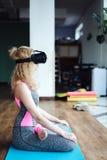 Frau in der Yogaklasse mit VR-Kopfhörer Lizenzfreies Stockfoto