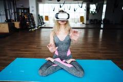 Frau in der Yogaklasse mit VR-Kopfhörer Stockbilder