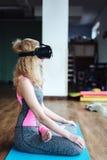 Frau in der Yogaklasse mit VR-Kopfhörer Stockfotografie