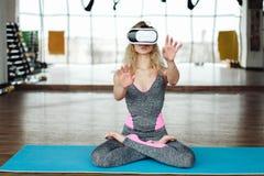 Frau in der Yogaklasse mit VR-Kopfhörer Stockbild