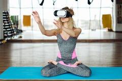 Frau in der Yogaklasse mit VR-Kopfhörer Lizenzfreie Stockfotografie