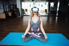 Frau in der Yogaklasse mit VR-Sturzhelm Stockbild