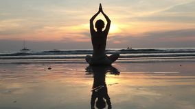Frau in der Yogameditationshaltung bei erstaunlichem Sonnenuntergang auf dem Meer stock footage
