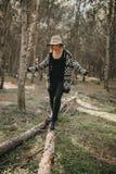 Frau in der zufälligen Kleidung gehend auf einen gefallenen Baumstamm in den FO Lizenzfreies Stockfoto