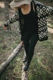 Frau in der zufälligen Kleidung gehend auf einen gefallenen Baumstamm im Wald Lizenzfreies Stockfoto