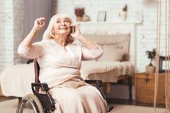 Frau des begeisterten Handikaps im Ruhestand, die zu Hause am intelligenten Telefon spricht lizenzfreie stockfotografie