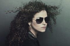 Frau des gelockten Haares mit Sonnenbrille Stockfoto