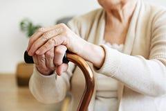 Frau des hohen Alters mit den Gesundheitsproblemen, die ihre Arme auf gehendem Stock stillstehen stockbilder