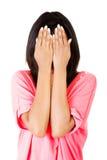 Frau des jungen jugendlich, die ihr Gesicht mit den Händen bedeckt Lizenzfreie Stockfotos