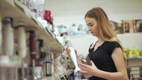 Frau des jungen Kunden nimmt eine Mischmaschine mit Schüssel von einem Gestell in einem Shop stock video footage