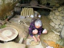 Frau des knetenden Bodens Quao-Tonwaren Dorfs vor dem Lehm keramisch Stockfoto