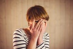 Frau des recht kurzen Haares, die ihr Gesicht hinter ihren Händen versteckt Lizenzfreies Stockbild