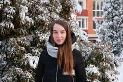 Frau des Winters in der Jacke unten im Winterpark auf Hintergrund der schneebedeckten Tanne stockfotografie
