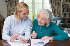 Frau, die älterem Nachbar mit Schreibarbeit hilft Stockbild