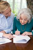 Frau, die älterem Nachbar mit Schreibarbeit hilft Lizenzfreie Stockfotos