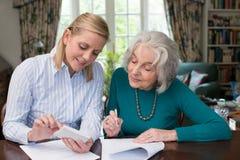 Frau, die älterem Nachbar mit Schreibarbeit hilft Lizenzfreie Stockbilder