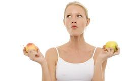 Frau, die Äpfel in den Händen isst und anhält Stockfotografie
