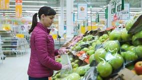 Frau, die Äpfel am Supermarkt wählt stock video