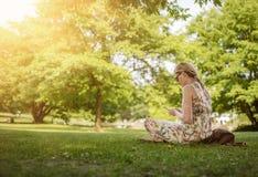 Frau, die öffentlich Park des Smartphone verwendet lizenzfreie stockbilder