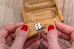 Frau, die ökologischen hölzernen USB-Blitz-Antrieb hält Lizenzfreies Stockfoto