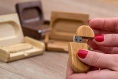 Frau, die ökologisches hölzernes ein USB-Blitz hält Lizenzfreies Stockbild