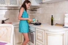Frau, die Öl auf Bratpfanne auf Ofen setzt Lizenzfreie Stockfotografie