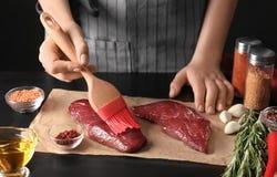 Frau, die Öl auf rohem Steak mit Silikonbürste aufträgt Stockfotografie