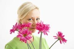 Frau, die über Blumen schaut. Lizenzfreies Stockbild