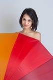Frau, die über buntem Regenschirm sich versteckt Stockfotografie