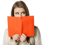 Frau, die über den Rand des geöffneten Buches späht Lizenzfreie Stockfotografie
