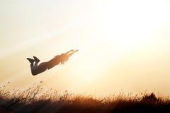 Frau, die über die Wiesennatur auf Sonnenuntergangschattenbildhintergrund fliegt stockbilder