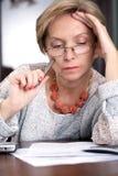 Frau, die über Dokumenten sitzt Stockbild