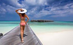 Frau, die über eine Anlegestelle in den Malediven geht Lizenzfreie Stockfotos