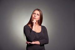 Frau, die über etwas erwägt Stockfotografie