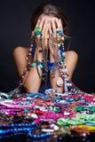 Frau, die über Haufen des Schmucks und des bijouterie schreit lizenzfreie stockfotografie