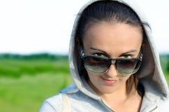 Frau, die über ihren Sonnenbrillen blickt Lizenzfreie Stockfotografie