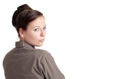 Frau, die über ihrer Schulter schaut Stockfotografie