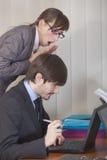 Frau, die über Mannschulter Computer betrachtet lizenzfreie stockfotos