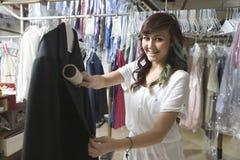 Frau, die über Mantel in der Wäscherei bürstet lizenzfreie stockfotografie