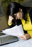 Frau, die über Rechnungen schaut Stockfoto