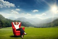 Frau, die über schöner Landschaft sich entspannt Stockfotos