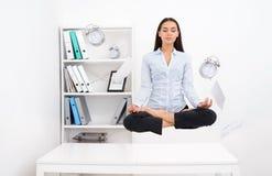 Frau, die über Schreibtisch frei schwebt und in lotos Position meditiert Stockbilder