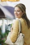 Frau, die über Schulter lächelt Lizenzfreies Stockfoto