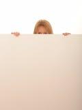 Frau, die über weißem Brett blickt Lizenzfreie Stockfotos