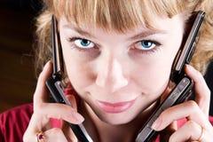Frau, die über zwei Handys spricht Stockfotografie