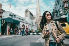 Frau, die überzeugt schaut und intelligentes Telefon verwendet lizenzfreie stockbilder
