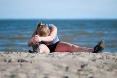 Frau, die Übung auf Strand ausdehnend tut Lizenzfreie Stockfotografie