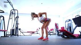 Frau, die Übung mit Barbell in der Turnhalle tut stock footage
