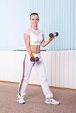 Frau, die Übung mit Dumbbells für zweiköpfige Muskeln tut Lizenzfreie Stockbilder